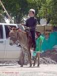Boy riding a donkey in Arslanbob